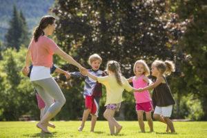 Yoga teacher and children exercising in the park.